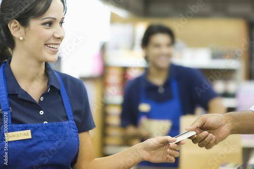 Cuadros en Lienzo  Closeup of a hand giving female employee loyalty card in supermarket