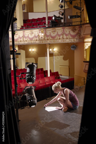 Photo  Side view of a young woman reading script on stage