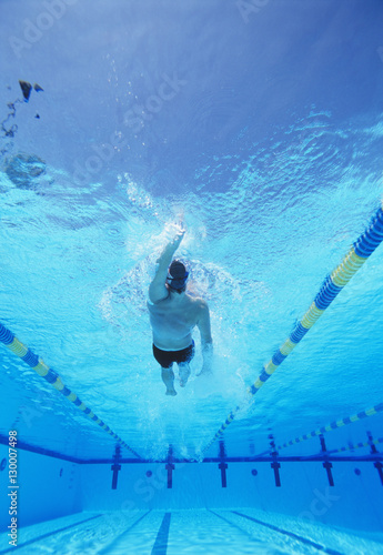 Underwater shot of young male athlete doing backstroke in swimming pool Canvas Print