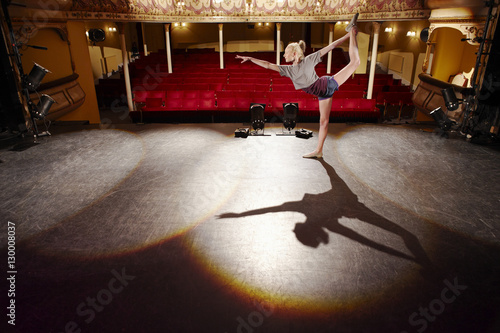Full length side view of a young woman stretching on stage Canvas Print