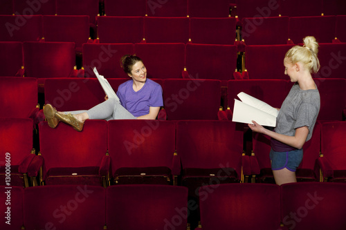 Photo  Two young women sitting in theatre stall with scripts
