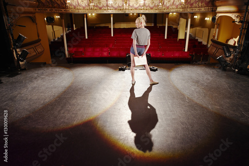 Photo  Full length of a young woman with script rehearsing on stage