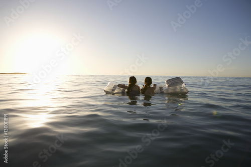 Fotografie, Obraz  Rear view of young twin girls paddling out to sea on air mattress
