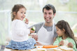 Happy father preparing sandwiches while daughters eating at home