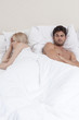 Young couple avoiding each other in bed
