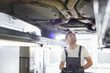 Mid adult male automobile mechanic worker examining car in workshop