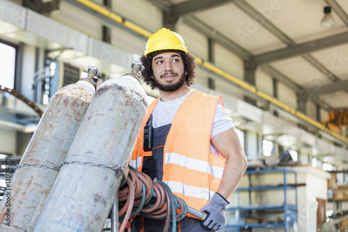 Fotografía Young manual worker moving gas cylinders in metal industry