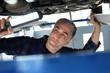 Mechanik samochodowy. Samochód w warsztacie, mechanik sprawdza stan podwozia.