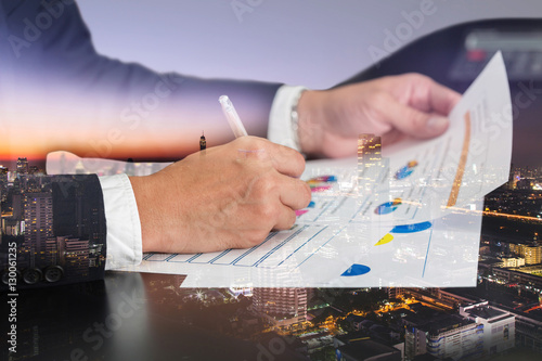 Fotografia, Obraz  Double exposure of businessman hand hold a pen write, review document, cityscape, urban and street in the night as review and working Concept