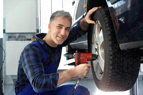 Obraz Wymiana opon w samochodzie. Mechanik samochodowy dokręca kluczem pneumatycznym koła w samochodzie. - fototapety do salonu