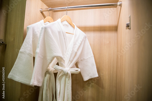 Fotografie, Obraz  two off white color bathrobes hanging in warmly design closet, r
