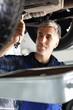 Mechanik wymienia olej. Mechanik samochodowy wymienia olej silnikowy w warsztacie samochodowym.