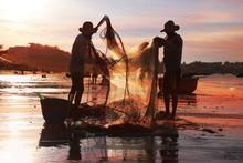Vietnamese Fishermen In The Setting Sun