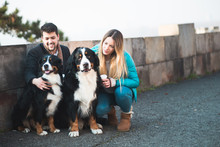 Young Couple Enjoying With Their Adorable Bernese Mountain Dog.