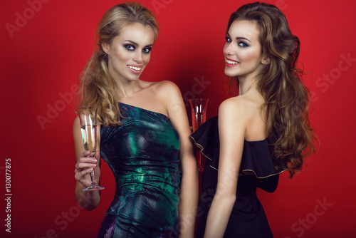 Fotografía  Portrait of two young beautiful glam women with provocative make-up and long hair wearing cocktail dresses with naked shoulders and holding glasses of champagne