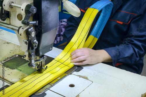 Fotografía  Industrial sewing machine sews a ratchet strap.