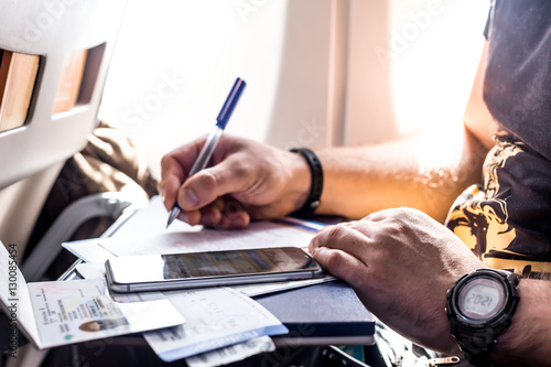 Photo  Man filling in immigration form sitting at airplane