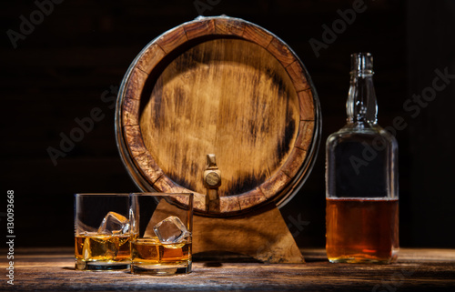 Stampa su Tela Glasses, bottle and keg of whiskey with ice cubes served on wood