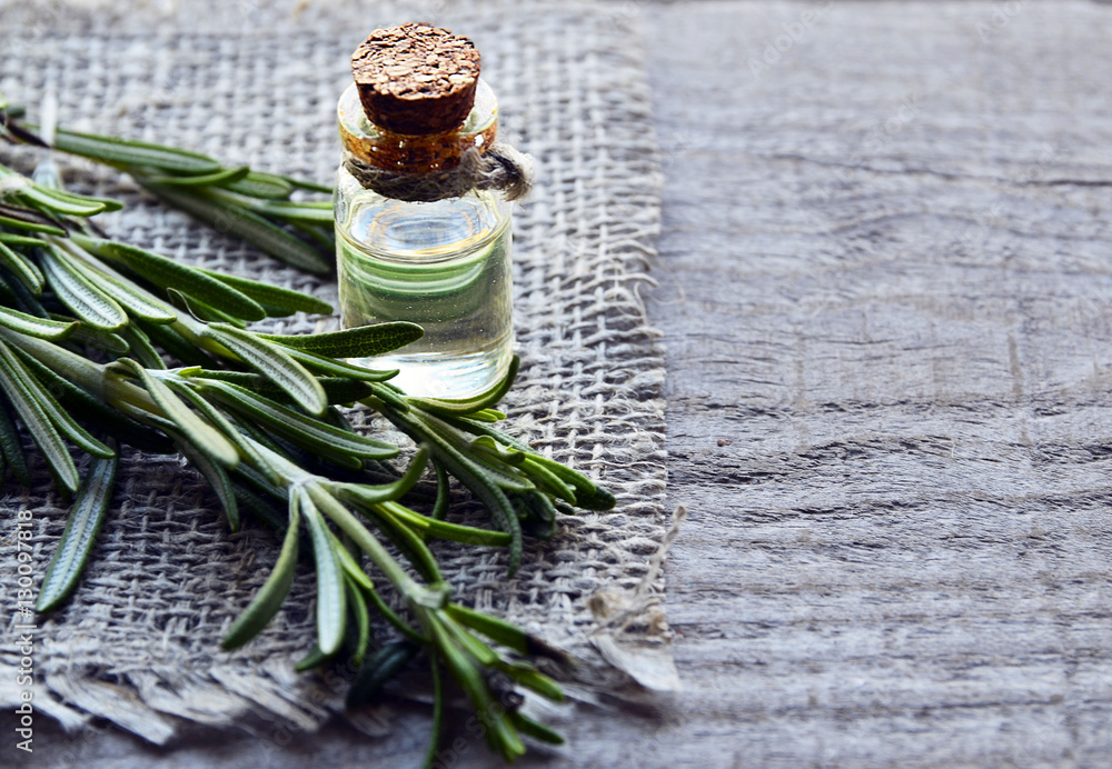Fototapety, obrazy: Rosemary essential oil in a glass bottle with fresh green rosemary herb on old wooden table.Rosemary oil for spa,aromatherapy and bodycare.Extract oil of rosemary.Selective focus.Copy space.