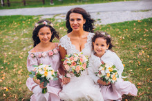 Cute Little Bridesmaids Holding Bouquet In Lawn With Bride.