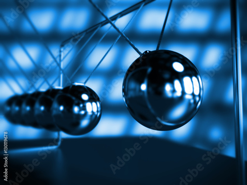 Fotografie, Obraz  Newton's cradle in motion, cradle surrounded by blue light