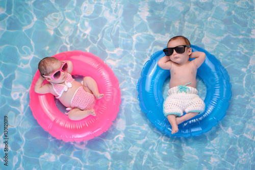 Fényképezés  Baby Twin Boy and Girl Floating on Swim Rings
