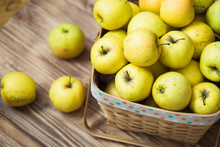 Golden Apples In A Basket On A Wooden Background