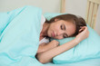 Beautiful young woman sleeping in the bed at home under the blue duvet with arms near her face.