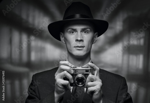 Front view of man holding vintage camera