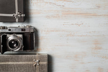 Vintage Photo Camera On Wooden Background With Gift Boxes. Top View. Copy Space