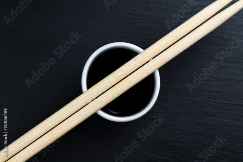 Soy sauce in small white bowl with chopsticks.