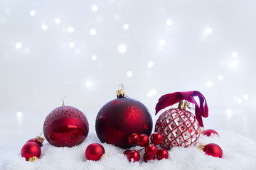 Christmas scene with snow - red balls with lights in background