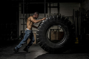 Fototapeta na wymiar Muscle Man in Jeans Pushing Large Tire