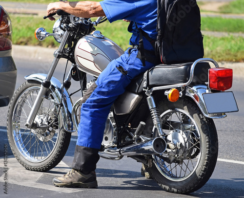 Foto  Man with a motorcycle on the street