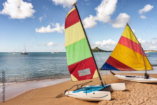 Colorful sail boat and catamaran rest on sandy beach Canvas Print