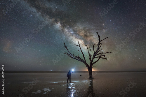 Stampa su Tela  Man Light Painting Ominous Tree Under The Milky Way Galaxy