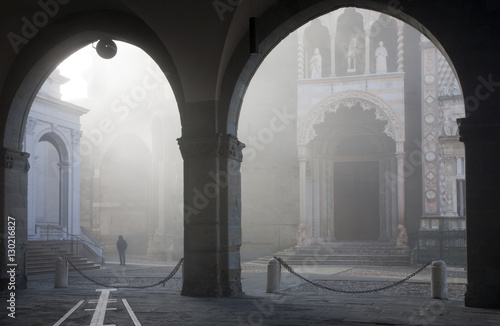 Cuadros en Lienzo Bergamo - rays between Duomo and cathedral under arch in upper town