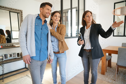 Photo  Couple with real-estate agent visiting house for sale