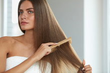 Brushing Hair. Woman Hairbrushing Beautiful Long Hair With Comb