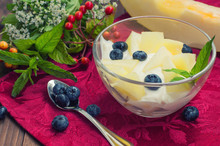 Curd With Melon, Blueberries And A Sprig Of Mint. Wooden Background. Top View. Close-up
