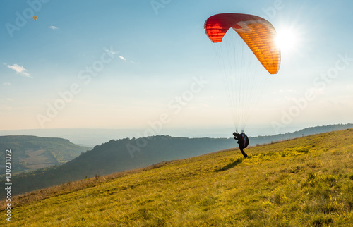 Spoed Fotobehang Luchtsport Paraglider in sunny day flying in Palava, hill Devin, South Moravia, Czech Republic