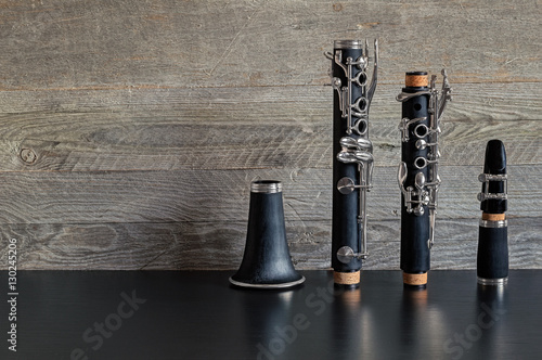Leinwand Poster Dismantled Clarinet on a Black Table