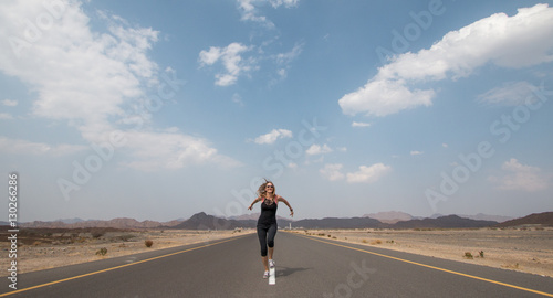 Photographie Young happy woman on an empty road in Oman desert.
