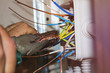 Electrician tightening the wire with pliers. installation works
