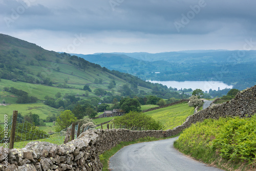 Fotografie, Obraz  Lake District, England - May 30, 2012: Rural road with stone walls on the side meanders through the landscape