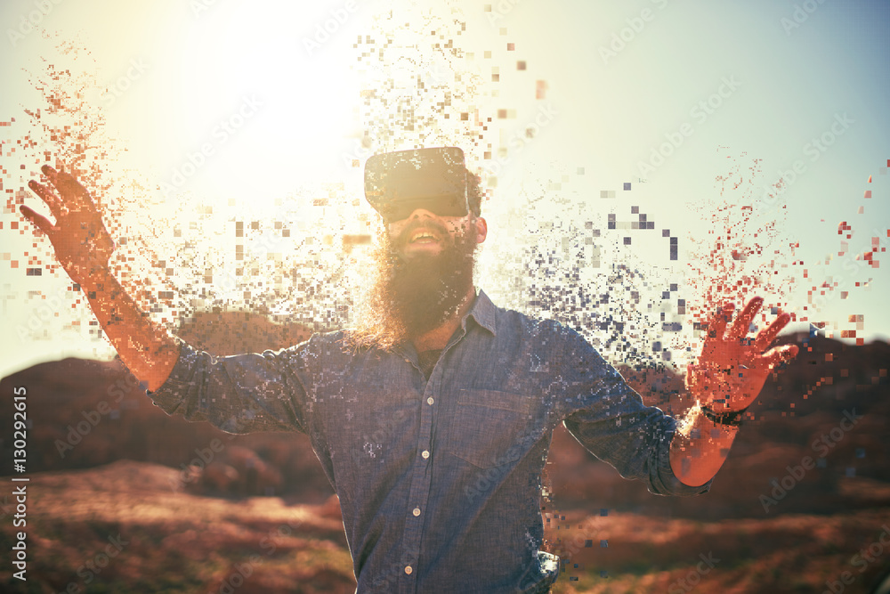 Fototapeta bearded guy in desert wearing vr glasses dissolving into pixels