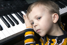 Dreaming Little Boy Sitting At The Piano