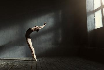 Fleksibilna baletana koja se proteže u mračnom osvijetljenom studiju