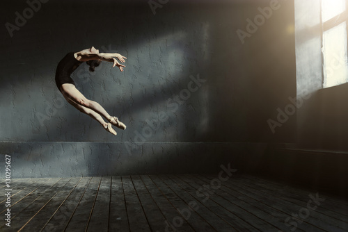 Professional ballet dancer performing in the dark lighted room Wallpaper Mural