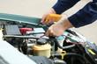 Mechanic hands with scan tool diagnosing car in open hood. Closeup